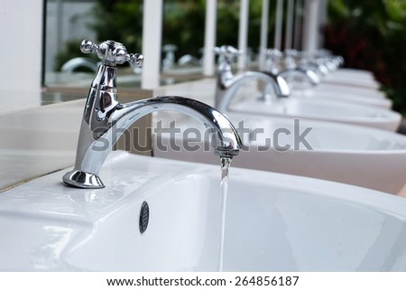 Water drop from chrome faucet. - stock photo
