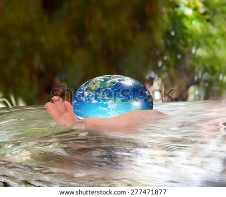 """Water drop shape in the hand ( drinking water crisis) """"Elements of this image furnished by NASA  - stock photo"""