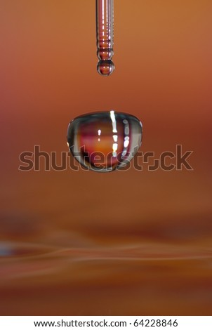 Water droplet macro in an orange environment - stock photo