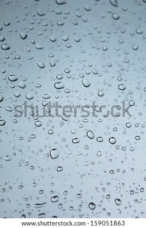 Water droplets on gray glass - stock photo