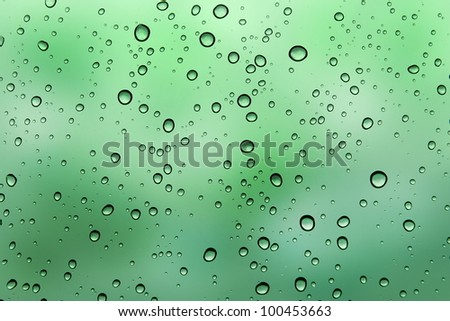 Water droplets on the green glass - stock photo