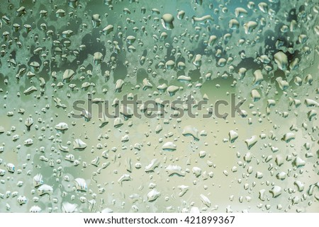 water droplets, water droplet on glass also looks like rain drop as water droplets on car window with light behind the water droplets or rain droplets with blurred behind the droplets - stock photo