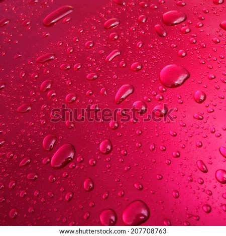 Water drops and droplets on a pink metallic paint car wet surface after the rain background - stock photo