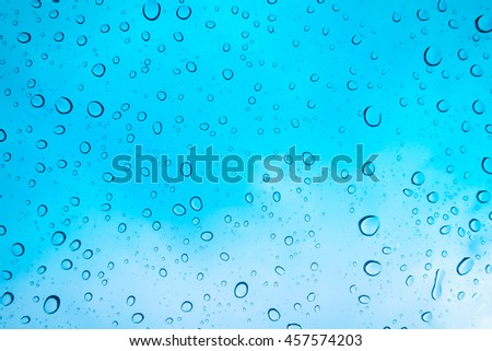 Water drops background. Water drops on glass window over blue sky - stock photo