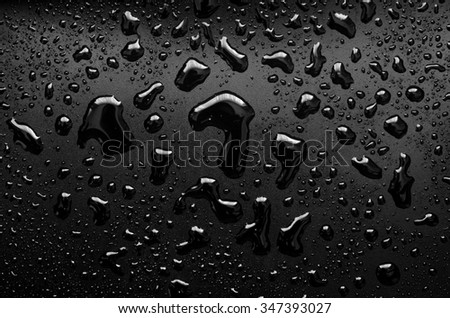 water drops on a black plastic surface - stock photo