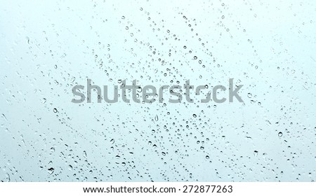water drops on glass against blue sky - stock photo