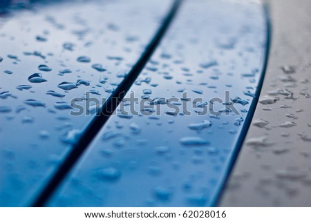 water drops on the surface of a blue car - stock photo