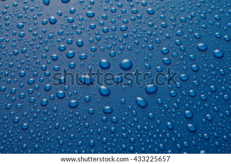 Water drops, raindrops or condensed dew on a polished blue metal surface in a close up overhead wide angle view - stock photo