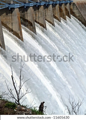 Water escaping over flood gates of a dam - stock photo