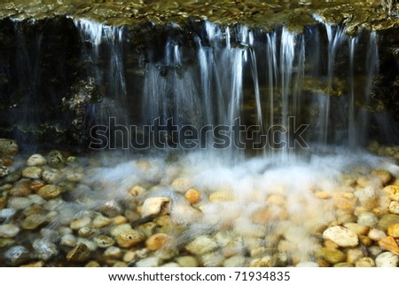 water fall and stones background. - stock photo