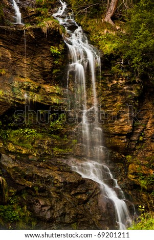 Water fall from a red-brown rock - stock photo