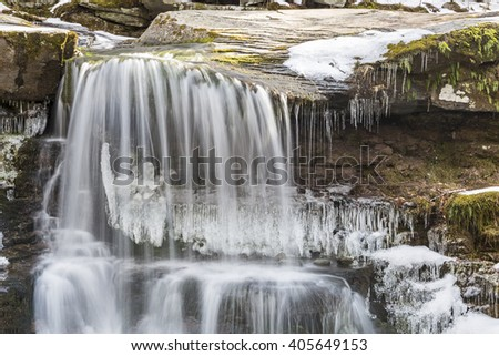 Water falls gently over partially frozen West Kill Falls in the Catskills Mountains of New York. - stock photo