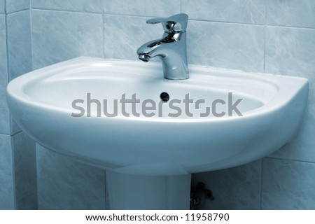 Water faucet and basin in blue tint - stock photo
