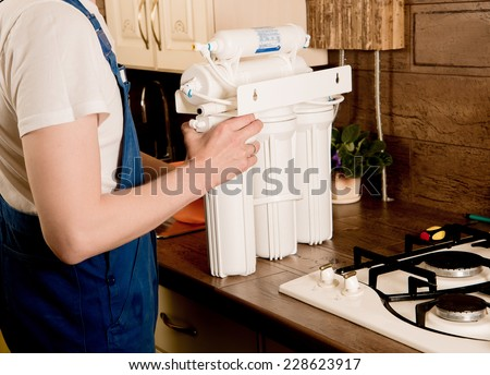 water filter. Locksmith installs water filter - stock photo