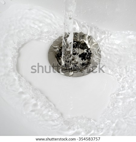 water flow into drain in bath,close up photo - stock photo