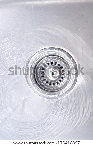 Water Flowing Down In The Hole In A Kitchen Sink  - stock photo