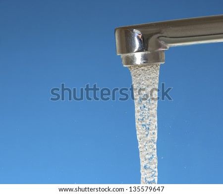 Water flowing from a tap on the blue background - stock photo