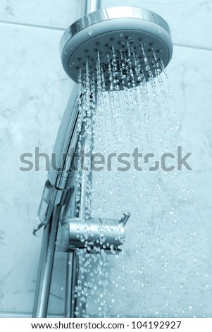 Water flowing from shower in blue tones - stock photo
