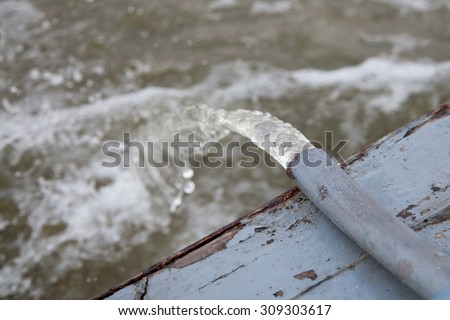 Water flowing from steel pipe into the river - stock photo