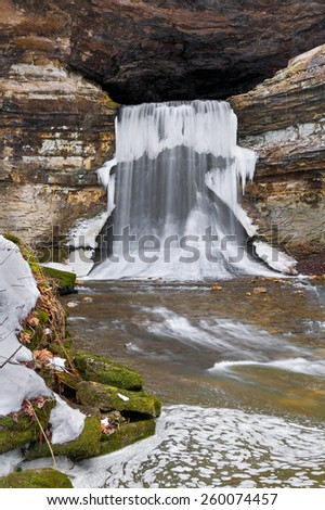 Water flowing from the mouth of Indiana's Porter Cave plunges over a thirty-five foot waterfall with icicles in winter. - stock photo