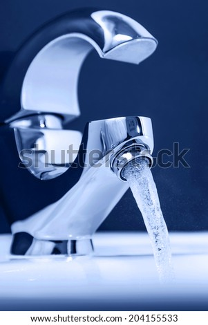 Water flowing out of the tap. Close-up, Shallow DOF - stock photo