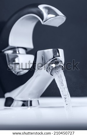 Water flowing out of the tap. Clouse-up, Shallow DOF - stock photo