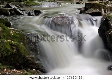 Water Flowing over Big Boulder Rocks - stock photo