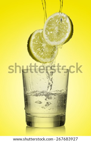 water flowing over lemon and fill a glass on yellow background - stock photo