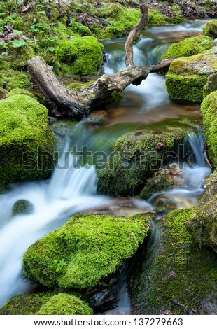 Water flowing over rocks covered with moss in small stream. - stock photo