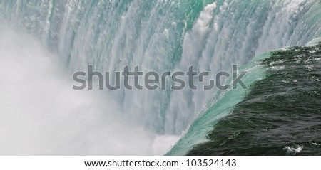 Water flowing over the edge at Niagara Falls. Horseshoe Falls, Niagara Falls - famous tourist landmark. Ontario, Canada - stock photo