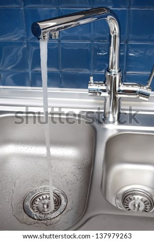 water flows from the tap in the kitchen - stock photo