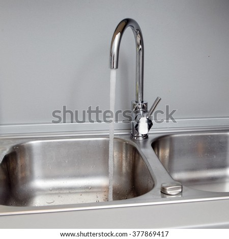 water flows from the tap to sink - stock photo