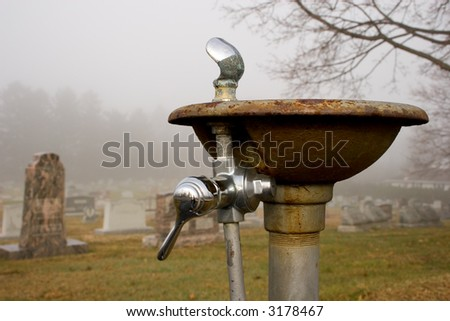 water fountain in a foggy cemetery - stock photo