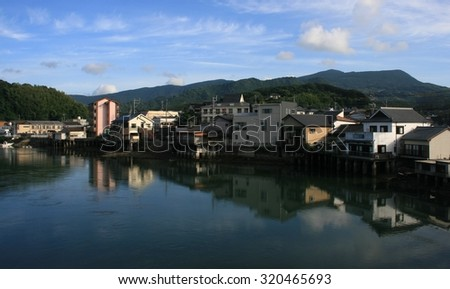 Water front buildings reflected in water with hills in the background, Sasebo, Japan - stock photo