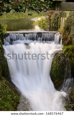 Water gently flowing under rural wooden bridge in Ruskington, Lincolnshire, England during early morning hours. - stock photo