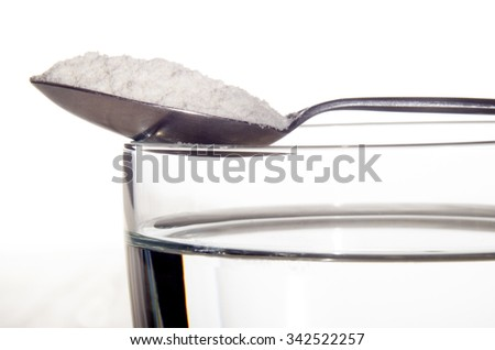 water glass with white medicine on a metal spoon - stock photo