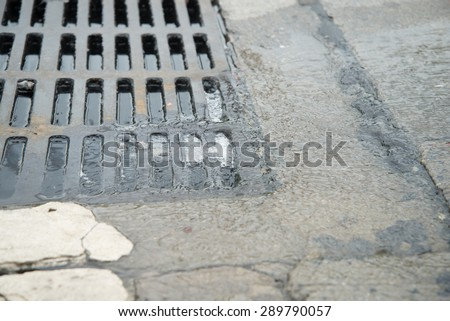 Water go down to the drain on the road - stock photo
