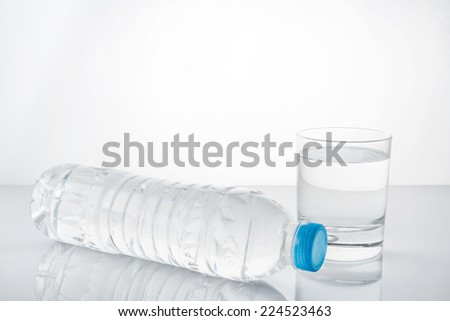 water in plastic bottle with glass - stock photo