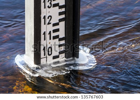 Water indicator on the river with a raised level of water in the spring. - stock photo