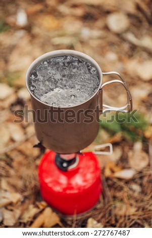 water is boiling in a pot on a gas burner in the forest - stock photo