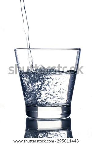Water is poured into a glass on white background - stock photo