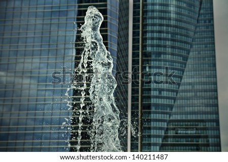 water jets, office building source, towers at background - stock photo