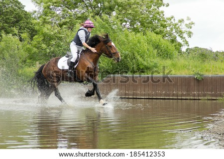 water jump-happy smiley rider and her horse enjoying riding through the water jump at an equestrian event on a summers day - stock photo