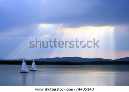 Water landscape with two yachts and sunshine in the background - stock photo