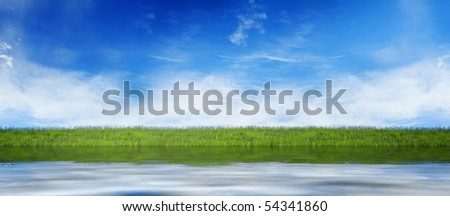 Water level with fresh grass and blue sky - stock photo