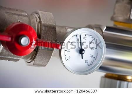 Water meters with red valve and metal pipes - stock photo