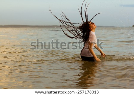 Water motion freeze woman in sunrise bathing - stock photo