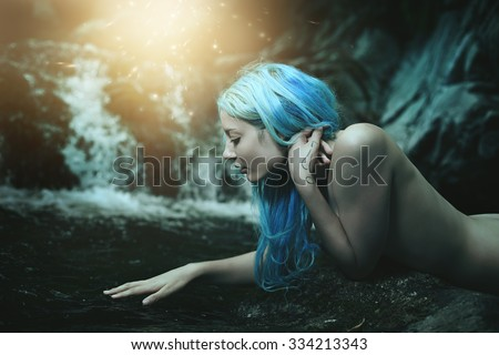Water nymph surrounded by magical lights . Fantasy and myth - stock photo