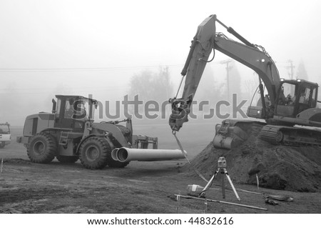 Water Pipe Delivery: Large fork lift delivers water pipe for burial on construction project - stock photo