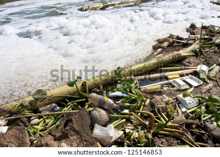 Water pollution - old garbage and pollution in river - stock photo